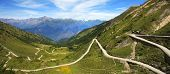 Panoramic view on unpaved road running through the hills and mountains of Alps in northern Italy.