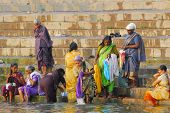 colorful hindu people bathing and doing laundry in holy ganges in varanasi