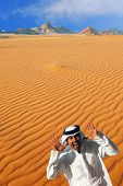 Traditional arabian man laughing, making funny face and playing peek-a-boo  in Wadi Rum desert, Jordan