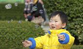 baby playing soap bubbles