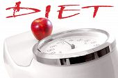 Time for dieting: red apple on white scale