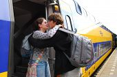 Cute couple in their twenties hugging and kissing each other goodbye at train station in Holland