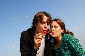 Concept: stay young! Young couple in their twenties blowing soap bubbles together with blue sky back
