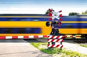 Fast speeding dutch train with motion blur and closed barrier and red warning signal