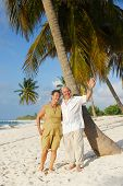 Happy senior couple embracing each-other and man greeting with his hand, enjoying retirement on tropical destination: Maria la Gorda beach on caribbean island Cuba poster
