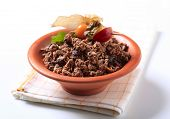 Brown ceramic bowl of muesli decorated with sallow thorn on folded napkin