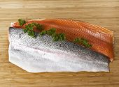 foto of steelhead  - Large fish fillets with parsley on bamboo board - JPG