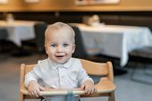 Cute Little Baby Boy In White Polo T-shirt Sitting In Wooden Baby Chair And Laughing At Cafe Indoors poster