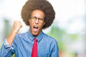Young african american business man with afro hair wearing glasses and red tie angry and mad raising poster