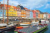 Tour Boat Sailing By Canal With Old Sailboats In Nyhavn Harbor, Peopel Walking At Sunny Embankment A poster