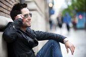 Jovem bonito sentado na rua falando ao telefone