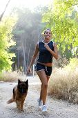 Young happy woman running with her dog