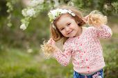 Beautiful Little Girl Outdoors In A Blooming Spring Garden On A Sunny Day.little Girl In Sunny Sprin poster