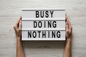 Female Hands Hold Modern Board With Text busy Doing Nothing Over White Wooden Surface, Top View. F poster