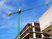 Huge Crane Near The Building Under Construction. Self-erecting Crane Against Blue Sky. Building Site poster