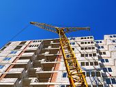 Self-erecting Crane Near The Building Under Construction. Construction Site. High-rise Brick Buildin poster