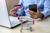 Close Up Mini Cart, Asian Businessman Holding Credit Card Using Laptop And Smart Phone For Online Sh poster