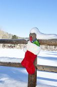 A Christmas stocking stuffed with presents hanging on a wooden fence in a wilderness resort mountain area.