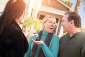 Hispanic Female Real Estate Agent Handing Over New House Keys to Happy Couple In Front of House. poster