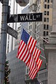 Focus on Wall Street Road Sign in New York City with USA flag in the background