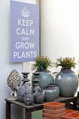 Stone Birds, Ceramic Vases, Flower Pots Standing On A Wooden Table And Hanging Picture keep Calm An poster