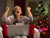 Happy Woman With Laptop Rejoicing Success In Front Of Christmas Tree