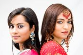 stock photo of bangla  - Two beautiful Bengali brides in colorful dresses isolated - JPG