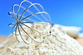 image of kitchen utensils  - Flour and whisk on kitchen board close up