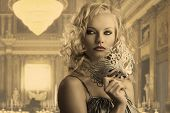 image of masquerade  - pretty blonde girl with curly hair takes one silver mask she is turned of three quarters at left looks at right and takes the mask with right hand - JPG