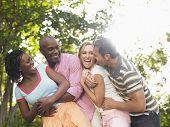 Dos alegre multiétnica pareja abrazándose y riendo en jardín