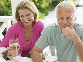 Meio envelhecido casal feliz segurando taças de vinho na mesa ao ar livre