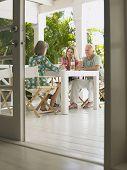 Tres personas de mediana edad, sentado en la mesa de la terraza
