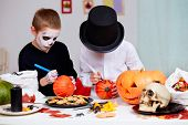 Photo of two eerie boys drawing on pumpkins at Halloween table