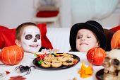 stock photo of antichrist  - Photo of two eerie boys looking at cookies on Halloween table - JPG