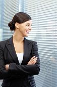 Image of formal businesswoman in suit looking through jalousie into neighbouring office