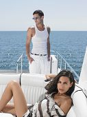 Portrait of sensuous young woman lying on sofa with man standing in yacht