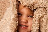 Sonriente niño escondido en la manta de la piel