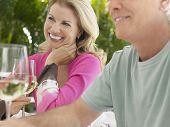 Feliz pareja envejecido medio sosteniendo copas de vino en la mesa al aire libre