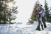 Full length of a romantic couple standing on snow covered hill