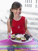 Portrait of a smiling little girl holding tray of cupcakes