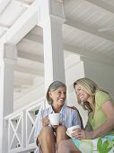 Dos mujeres edad medias felices sentado en la terraza con tazas de café