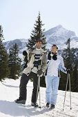Full length of a skiing couple with skis standing on ski slope