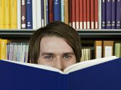 pic of shelving unit  - Closeup portrait of a young man peeking over opened book in library - JPG
