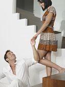 Smiling young man looking up at woman on stairs in the house