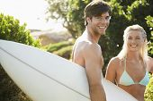 Portrait of young man carrying surfboard with girlfriend in bikini at beach