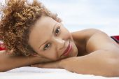 Closeup portrait of happy young woman lying on massage table outdoors