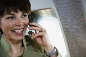 Businesswoman using cell phone on private airplane