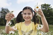 Portrait of happy young girl holding daisy chains in meadow