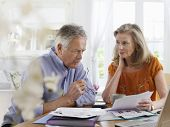 Mature couple with bills sitting at dining table in house