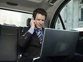 Young businessman using mobile phone and laptop in car